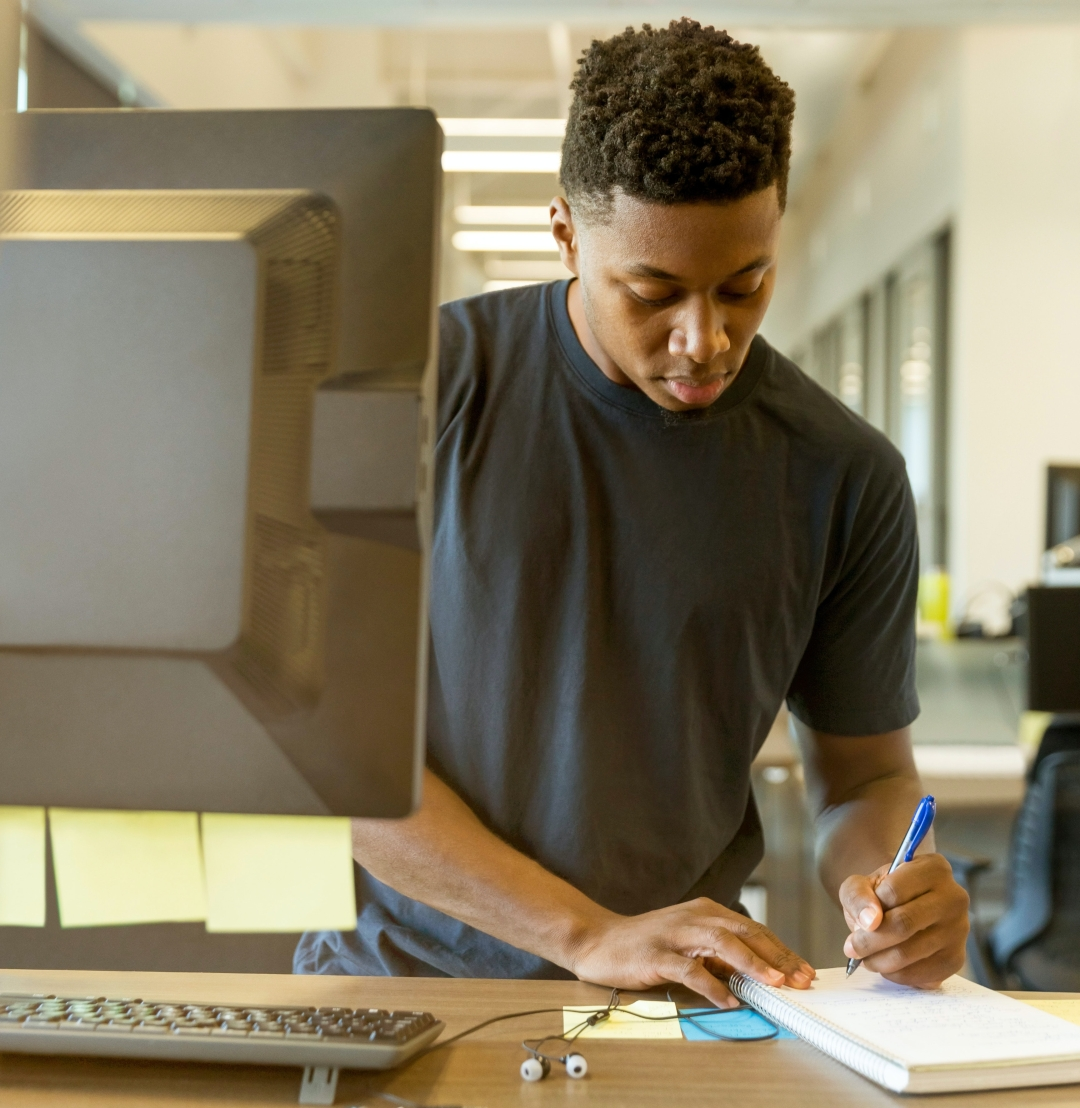 A young man stands at a desk with a computer and writes on a notepad.